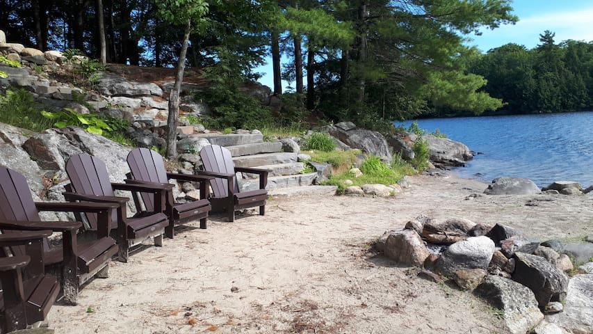 Private beach with Muskoka chairs and fire pit.