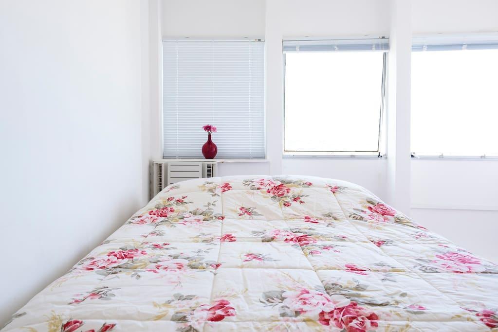 cama de casal, armário, ar cond. poltrona e ventilador de teto.