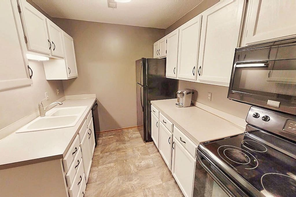 White kitchen with dishwasher, disposal, range/oven, microwave oven, and refrigerator with ice maker