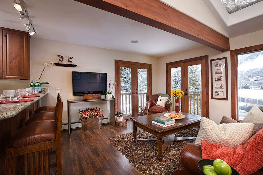 Living room with flat screen TV and vaulted ceilings.