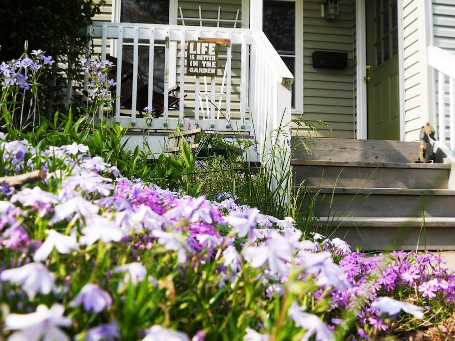 Porch overlooks a beautiful garden of flowers in the warm months