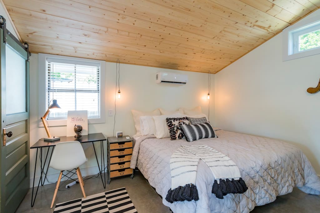 King bed and remote controlled Heat/AC unit under pine ceilings and finished concrete floors.