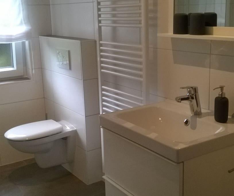 Das frisch sanierte Badezimmer mit ebenerdige Dusche.