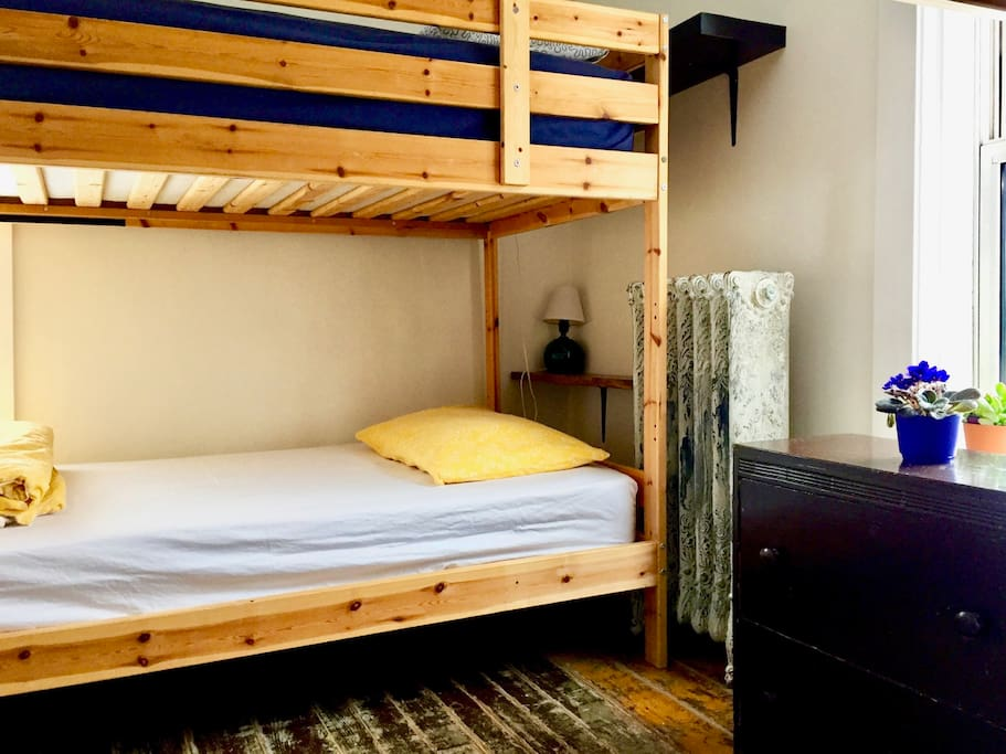 Shared 4-bed dorm with area lamps & shelf for each bunk