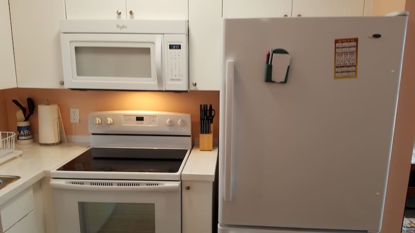 Kitchen equipped with full size stove and oven, refrigerator, microwave and coffee maker.