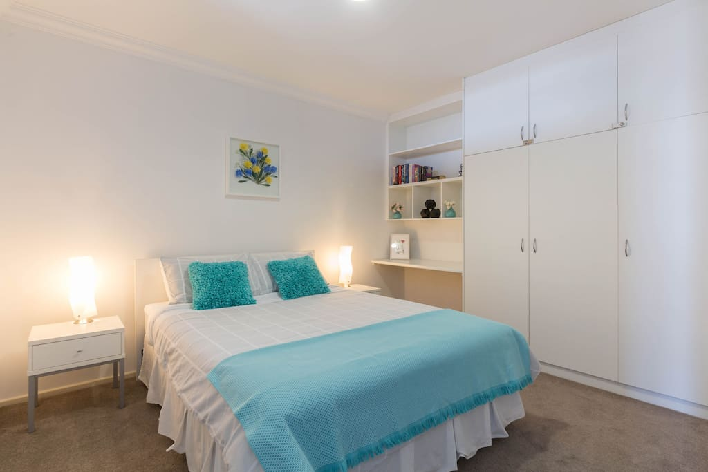 Bedroom with Queen sized bed, large wardrobe and desk.