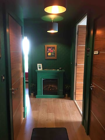 """Entrance hallway which doubles as a is quirky fun """"darts room."""" Painted entirely in a green reminiscent of old pubs, a cheery green fireplace welcomes guests."""