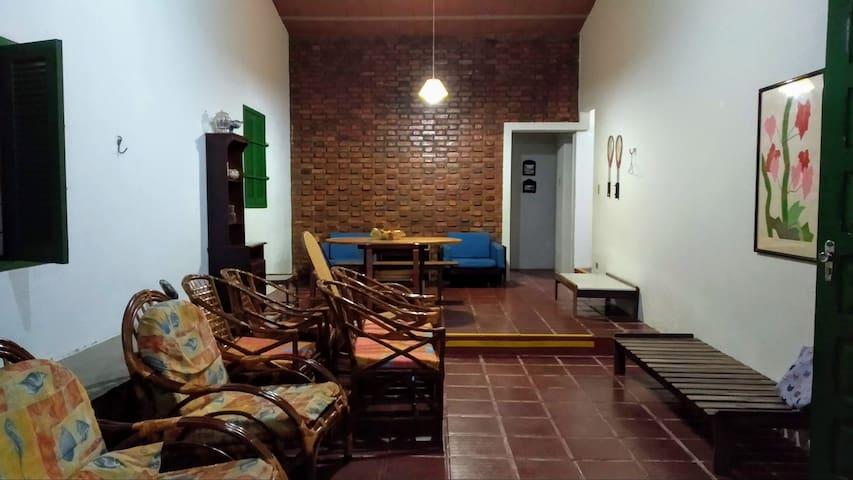Sala enorme. Ao fundo, acesso para 3o. WC social, lavabo e cozinha. à direita, entrada do corredor para os quartos.