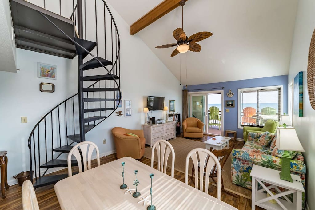 Nicely decorated living and dining area where you will relax after vacation days.  Spiral stairway to the upstairs sleeping loft.
