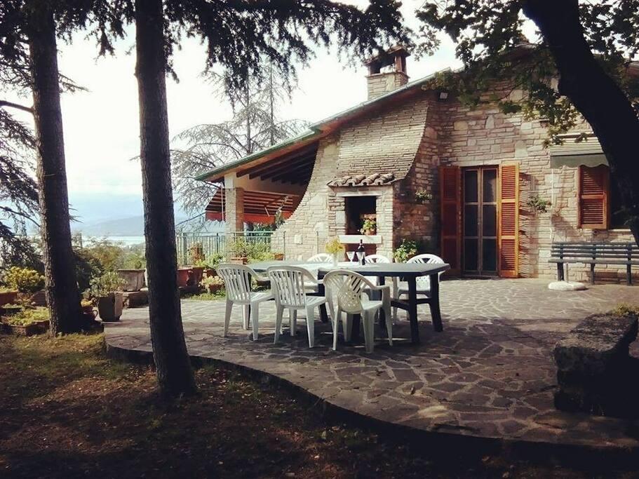 spazio esterno attrezzato con tavolo, camino in muratura per mangiare e riposarsi con vista diretta sul lago.