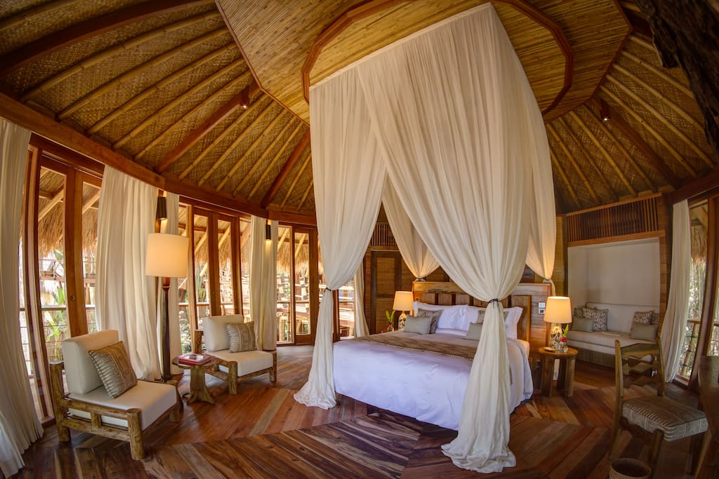 A Sumba-chic bedroom with traditional thatched roof