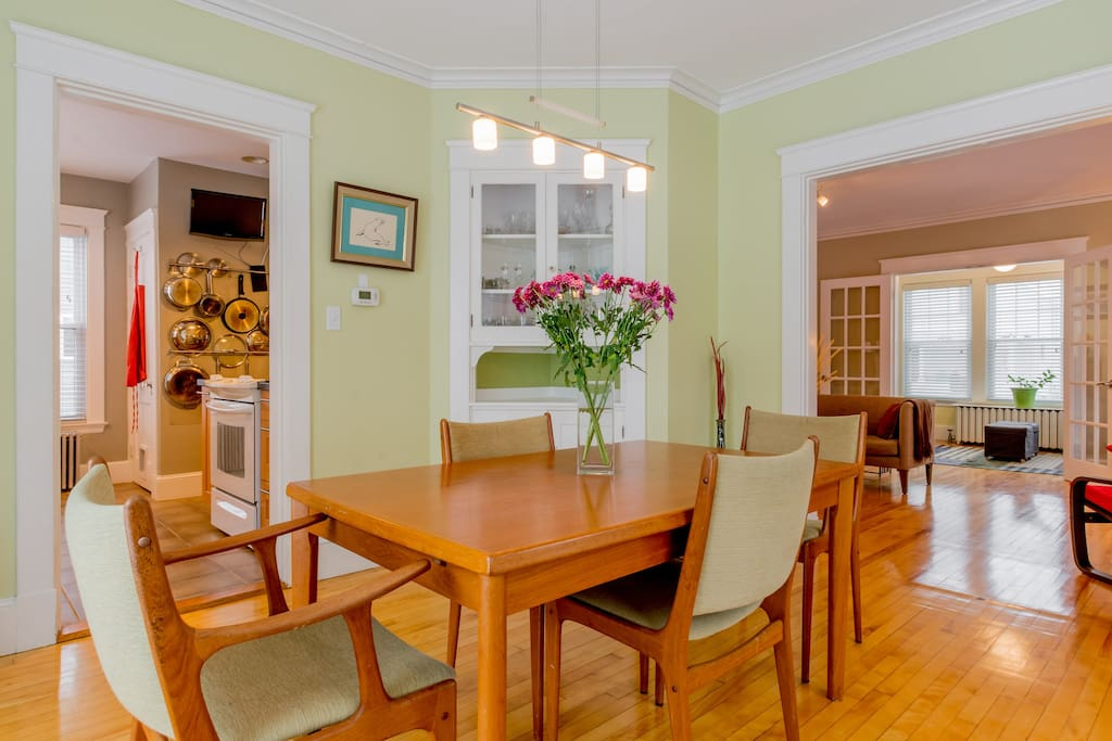 Dining room with teak dining table. Built in cabinet with bar glassware.