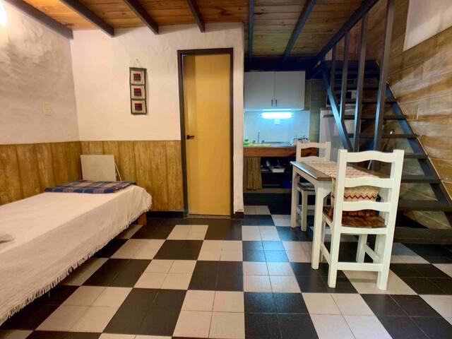 plata baja: cuenta con una mesa para que se puedan sentar 3 personas. una pequena cocina, el bano y una cama de una plaza el cual tambien se utiliza como sofa.