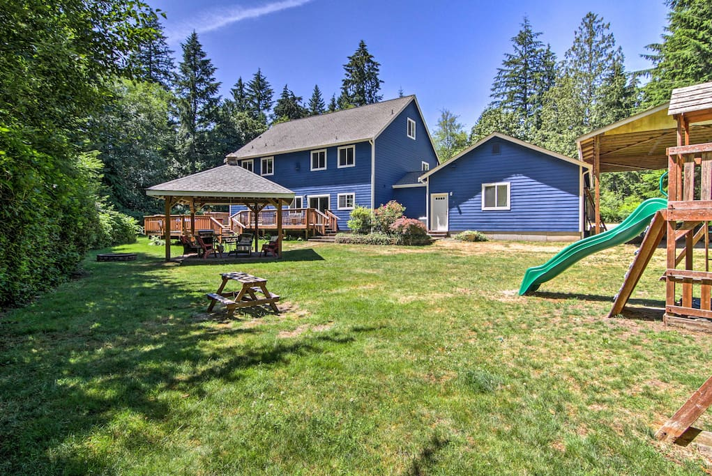 The large backyard features a covered patio, fire pit, and playground.