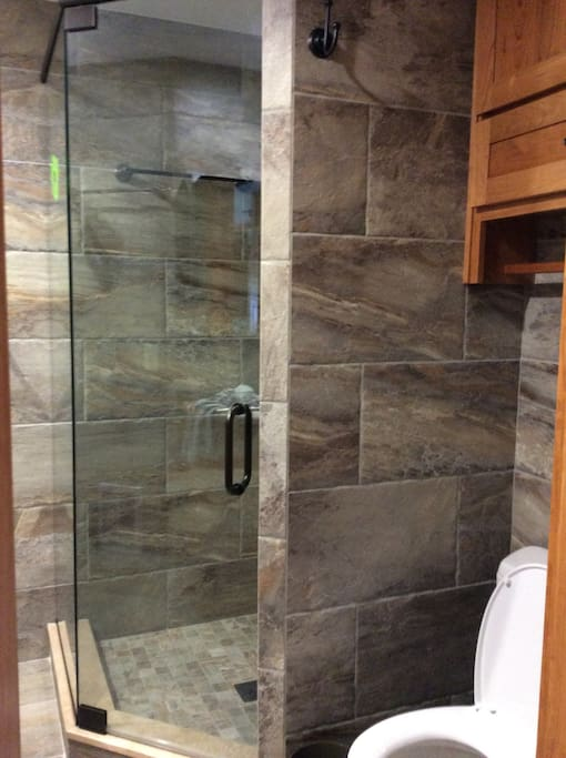 Bathroom downstairs with heated floor, shower head, hand held shower and washer/dryer