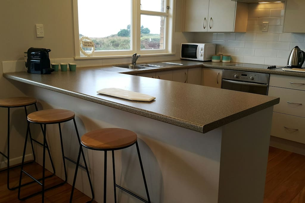 Modern kitchen, stainless appliances (double-door fridge, dishwasher, oven), microwave and Nespresso all with stunning sea views