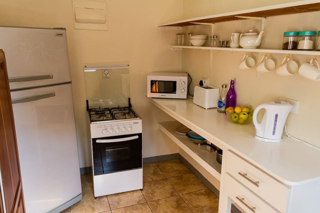 Kitchen with fridge, gas stove, microwave, toaster and kettle.
