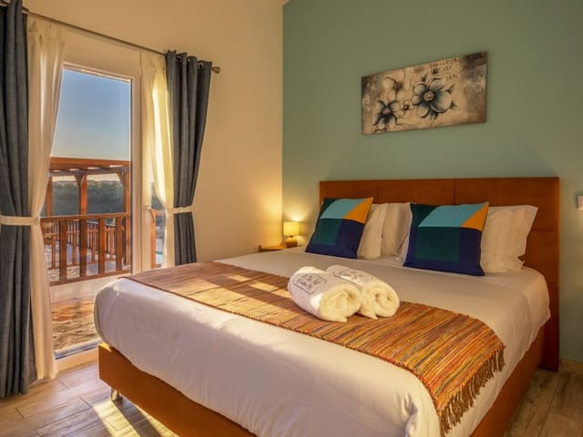 Guestroom Terrace Deluxe; the comfortable bed and the view over the sun terrace.