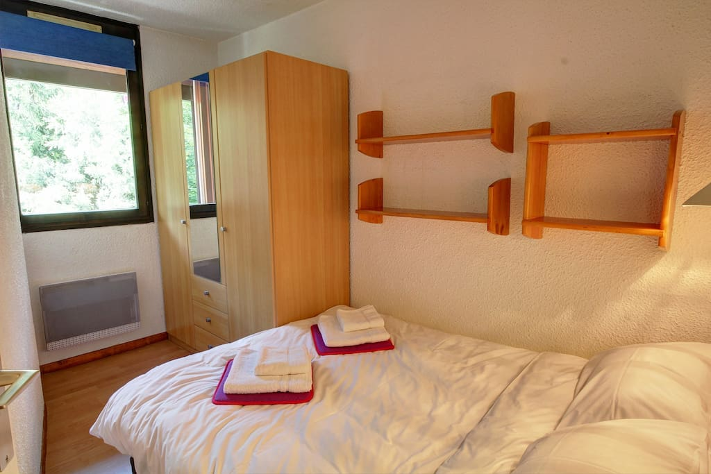 Double bed and a three-door wardrobe in the bedroom.