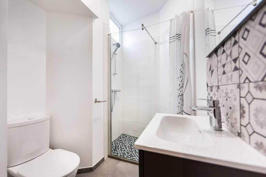 Confortable salle de bain avec une belle douche à l'italienne.