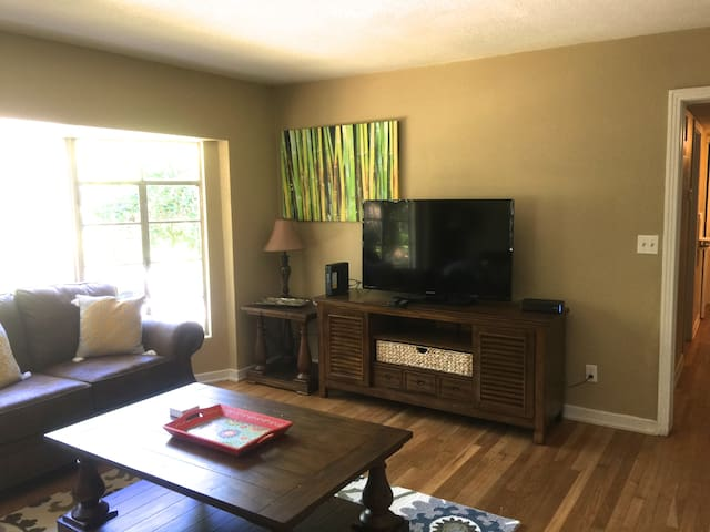 """Comfortable living area with 50"""" television and bay window that overlooks a peaceful pond."""