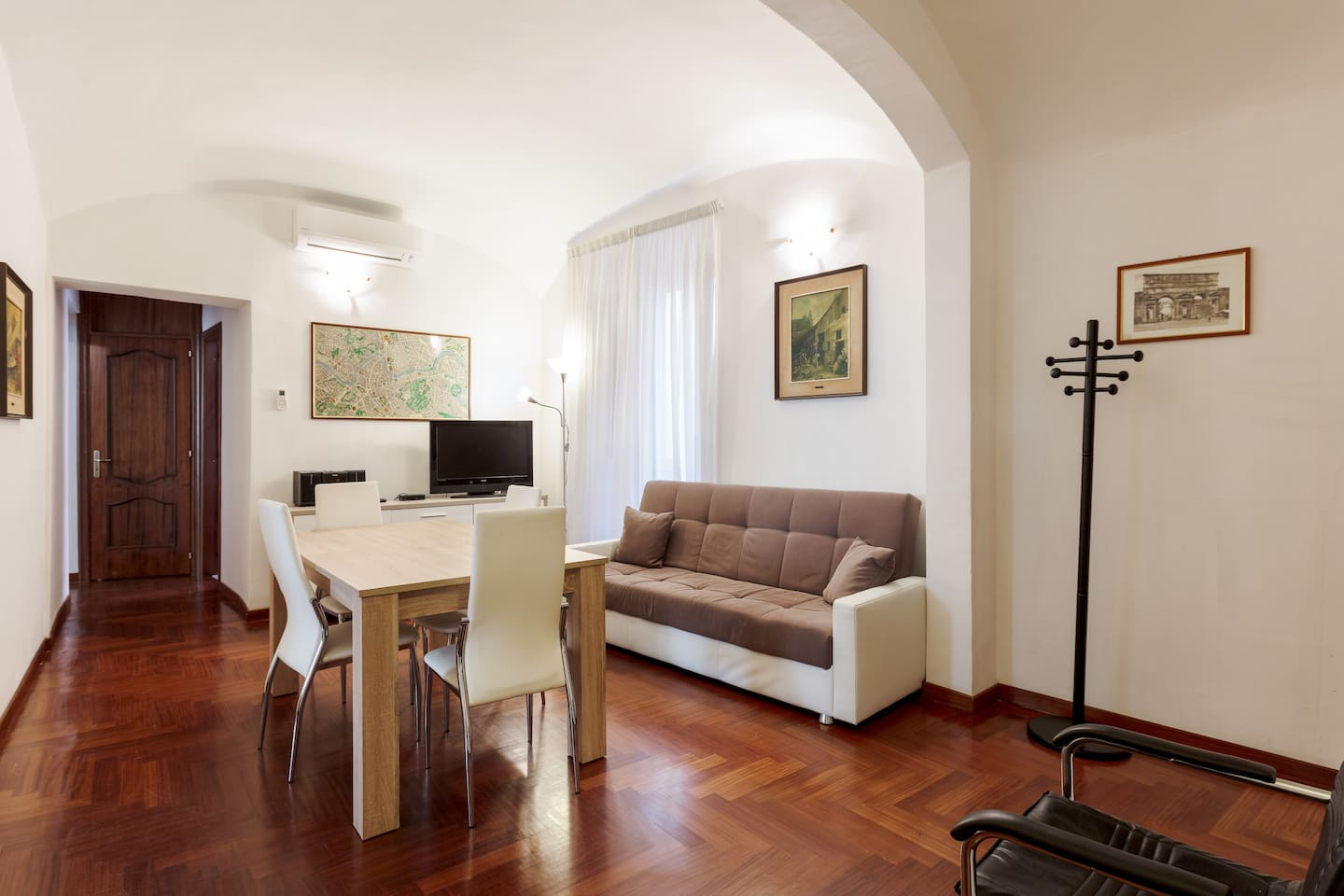 The living room: the dining table, AC, TV & sofa