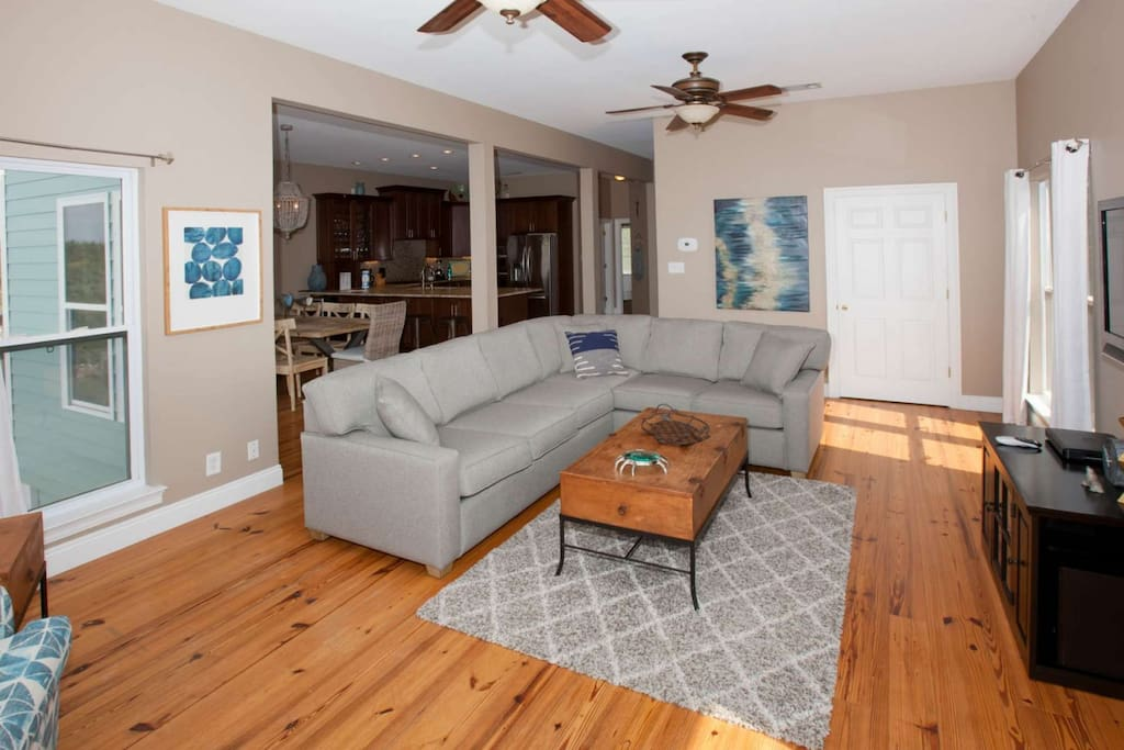 First floor living room with wood floors, ceiling fans and sectional sofa