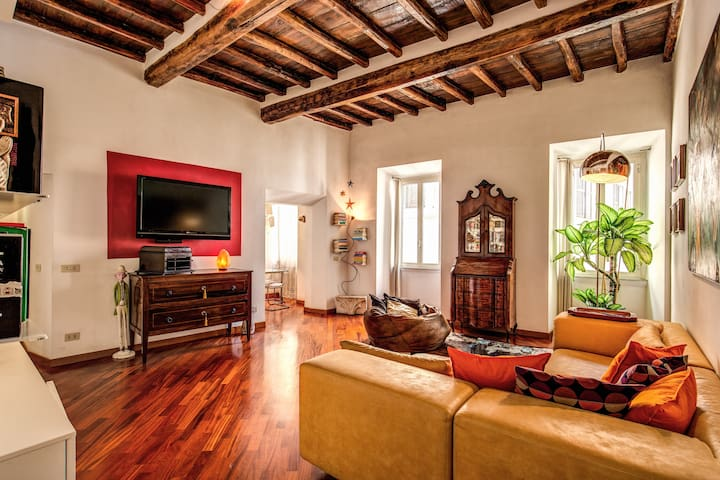 TV in big living room with parquet floors and original wooden beams of the 1500
