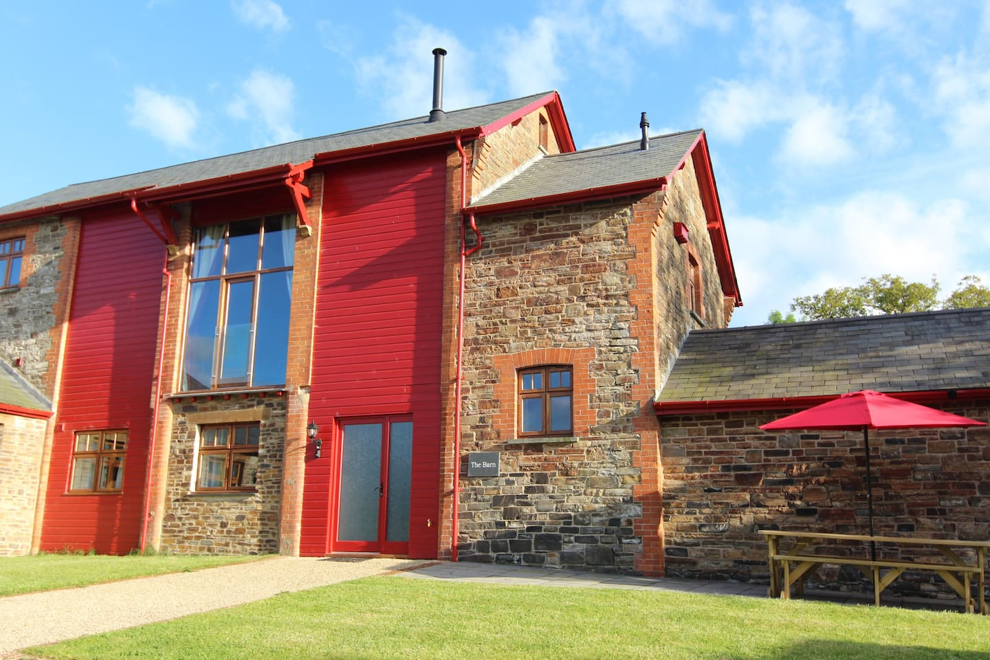 The Barn, with seating area, benches, BBQ and ample parking.  There is a large vaulted lounge on the first floor with TV/DVD player and log burner.  A second TV room and upstairs WC.   Three bedrooms, one en suite.  Underfloor heating throughout.
