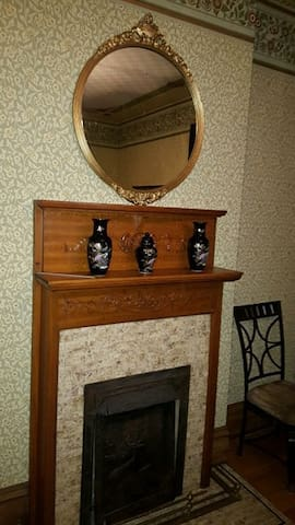 Beautiful fireplace in guestroom 1 with antique gold mirror adds to the charm.