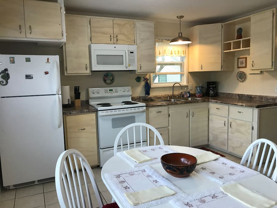 The kitchen is fully equipped and contains a dining area