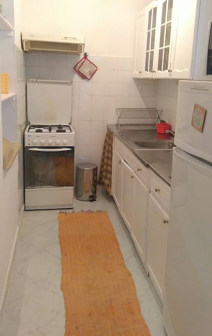 Kitchen with stove, fridge and microwave