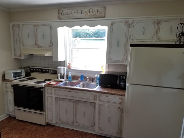 Full kitchen with dishes, silverware, pots, pans, glasses and charm.