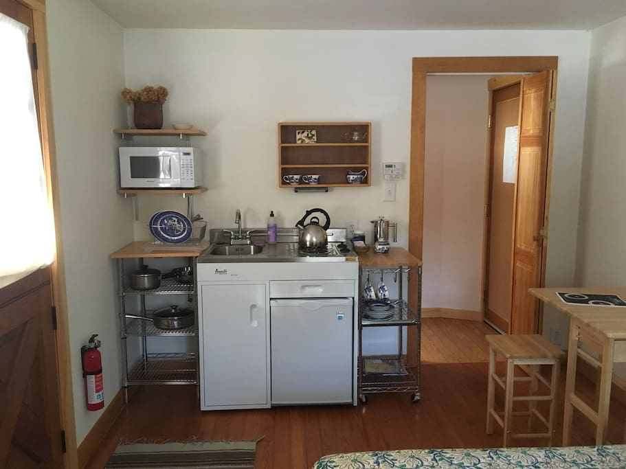 Studio kitchenette (with stovetop, sink, mini-fridge, microwave and tea/coffee-makers), open table and hallway to full bath