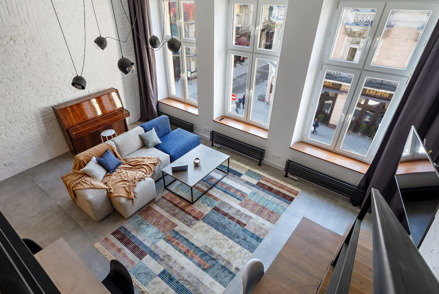 The view from the loft is two fold: the outside scene through the three tall windows and the spacious interior below.