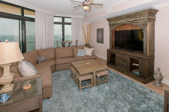 Living room with large flat screen TV, coffee table with 4 stools and ceiling fan