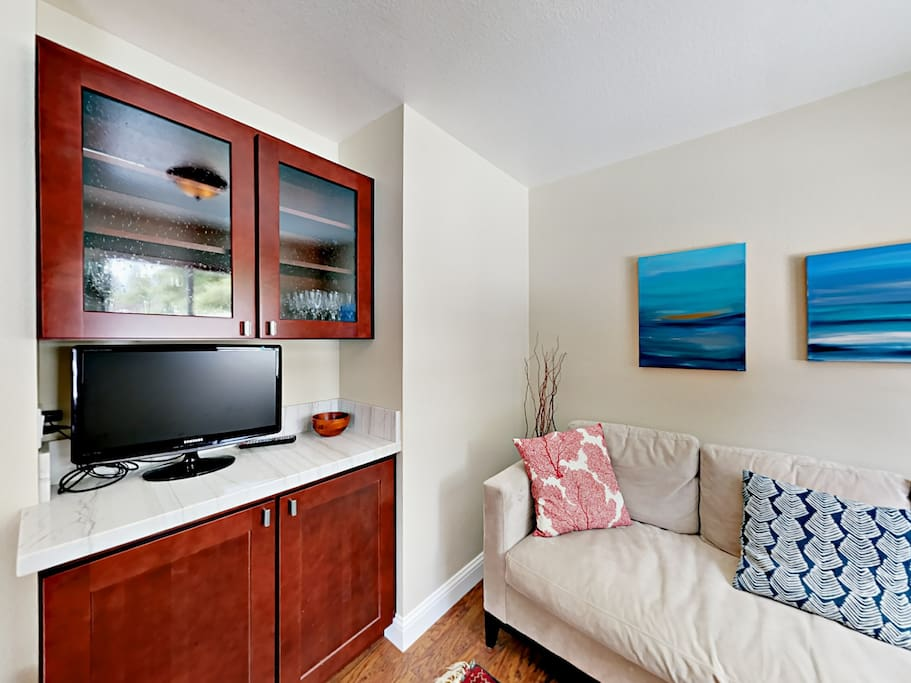 """Welcoming living room with 21"""" TV and comfortable sofa."""