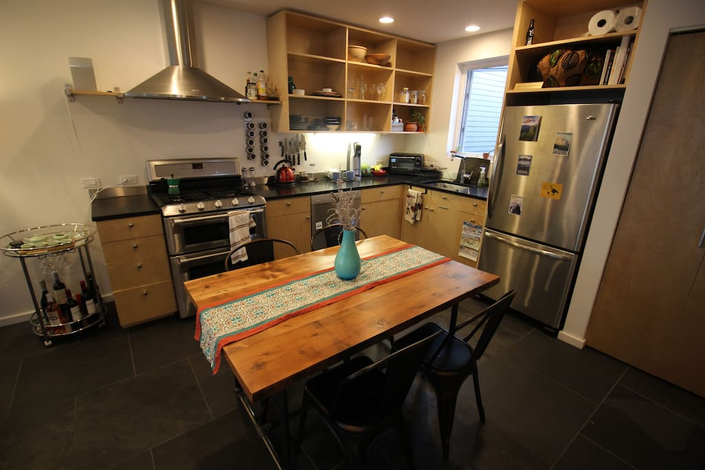 Fully stocked open plan kitchen with reclaimed wood hand-made table