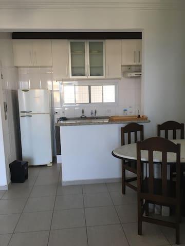 Cozinha equipada com geladeira, fogão, microondas, liquidificador, espremedor de laranjas e utensílios de cozinha.
