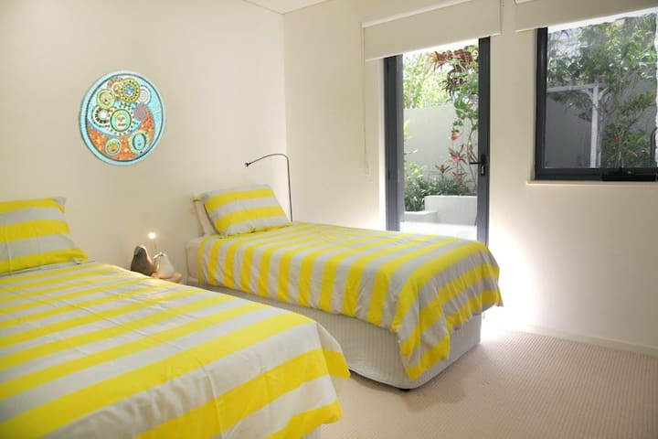 Bedroom 2 with single beds and a private courtyard