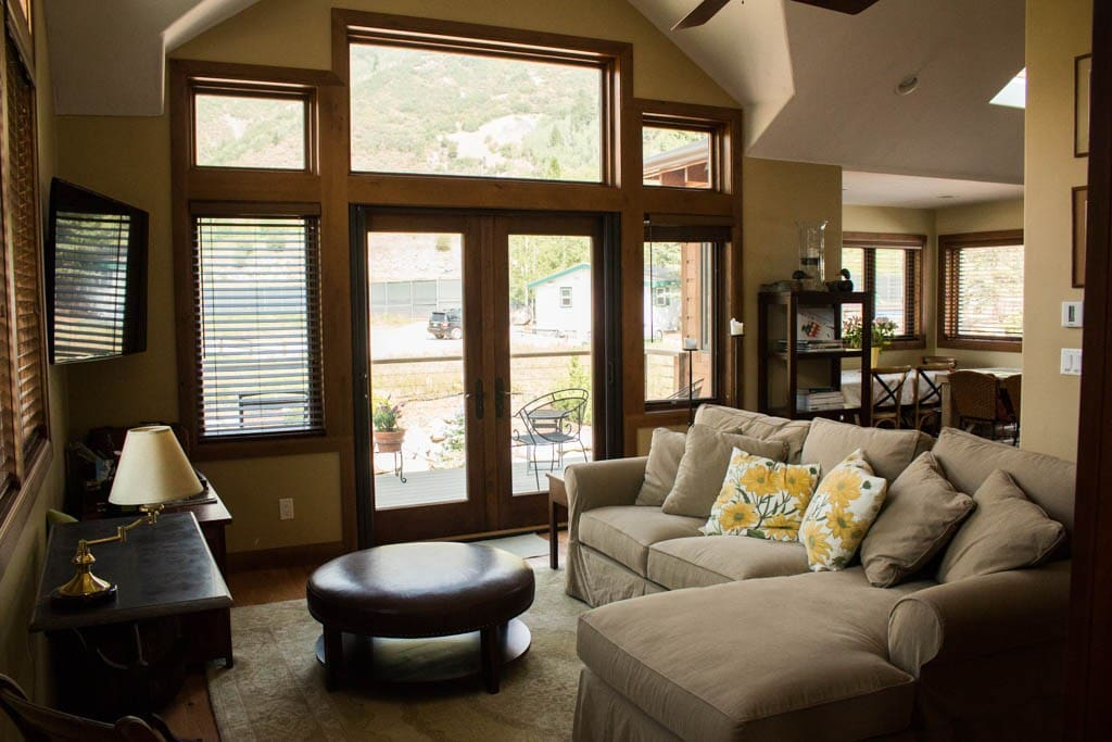 Living room with large couch and french doors that open out onto the deck.
