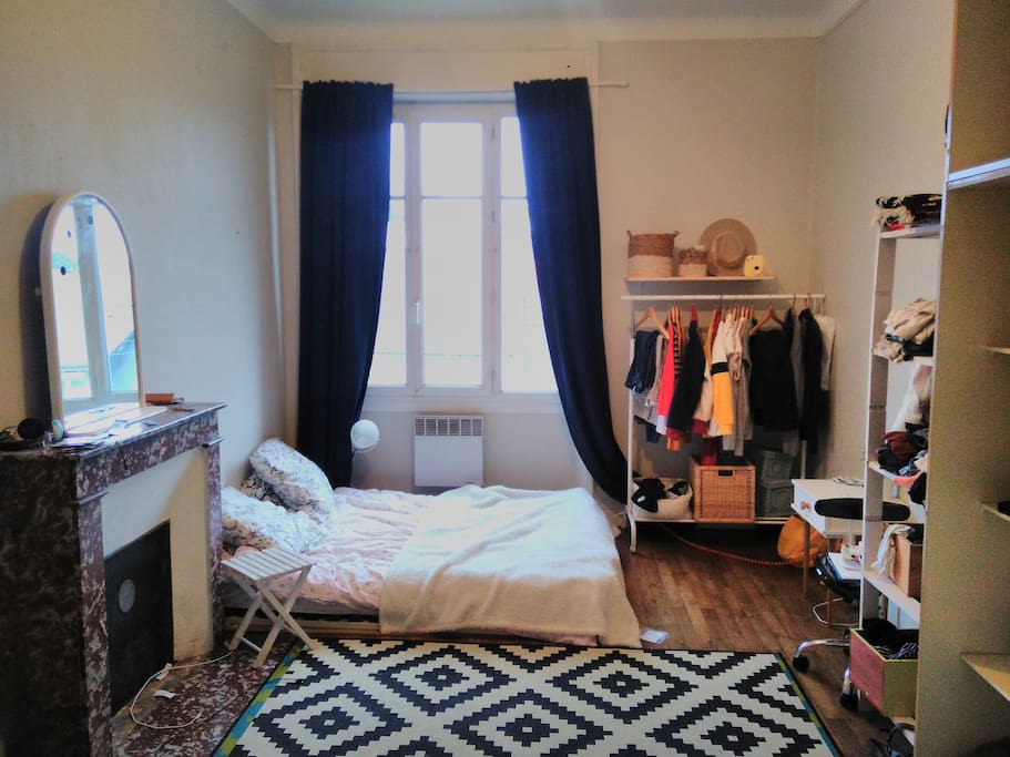 Chambre spacieuse sur parquet et cheminée décorative
