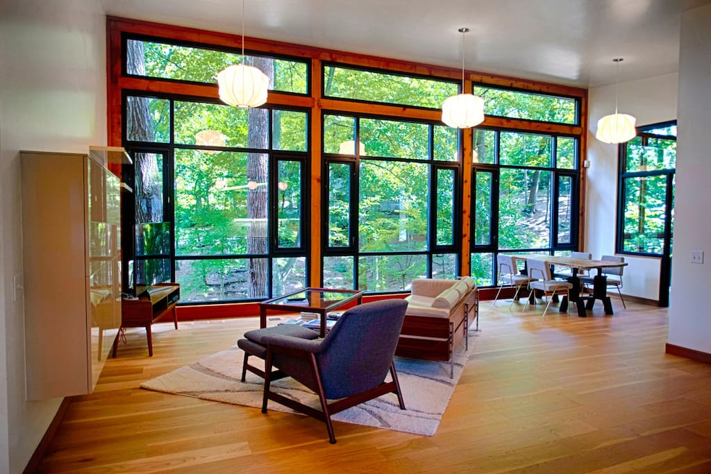 The floor-to-ceiling windows open up to the forest air and sounds.