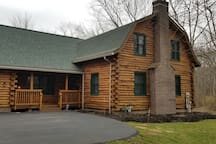 Front of the house.  Newly paved driveway, barnstyle log home.