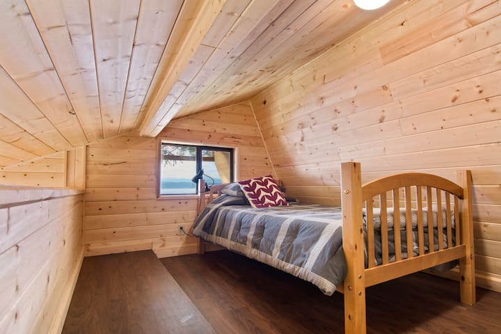 Upstairs sleeping loft with 2 single beds and a view.