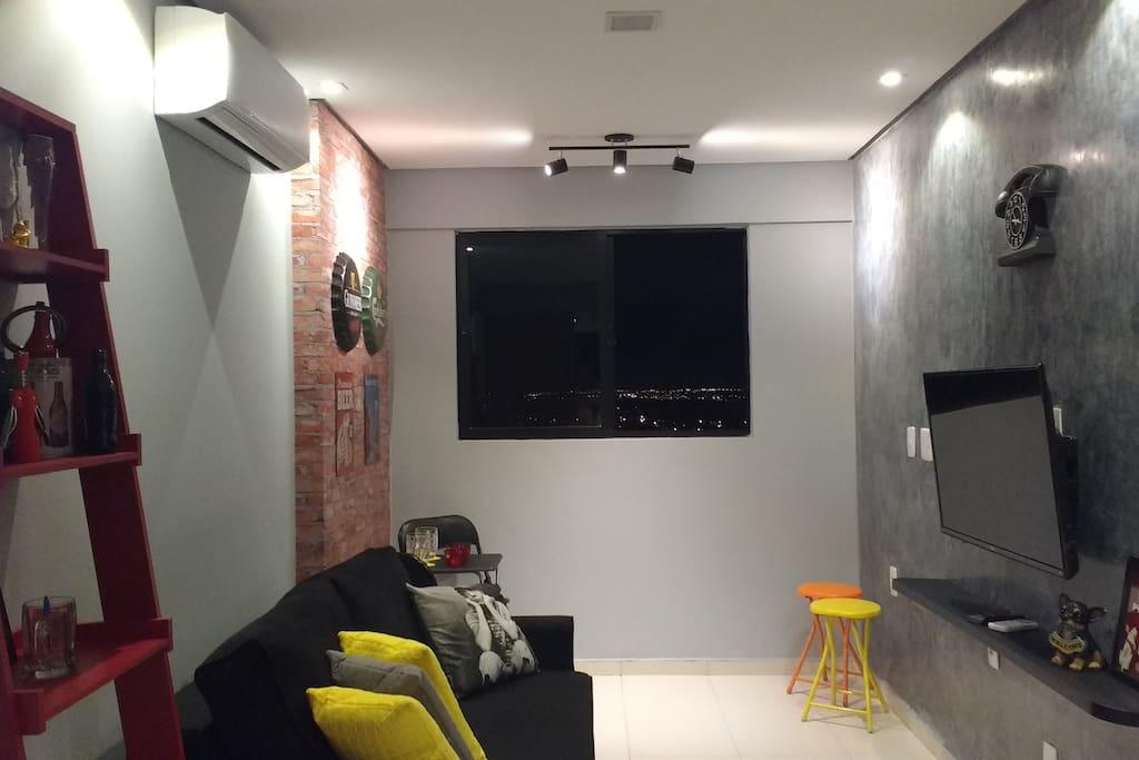 Sala com sofá, tv, wi-fi e ar condicionado.