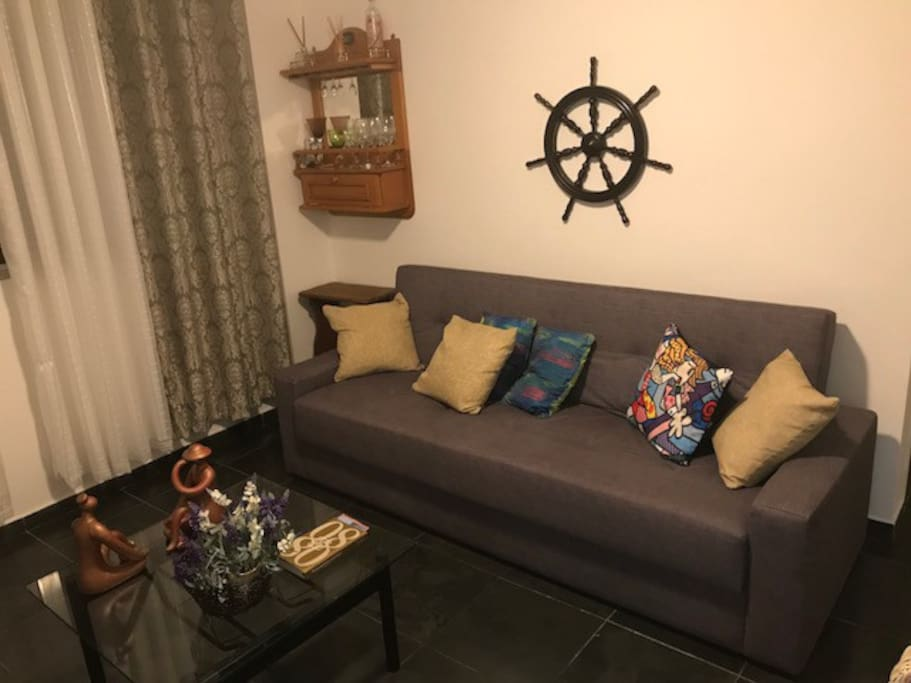 Sala com sofá cama casal e ventilador de teto e TV