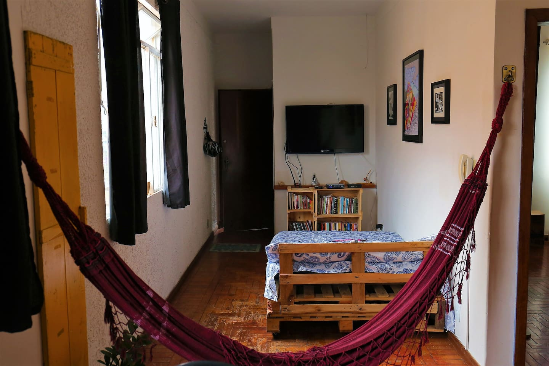 Sala de estar com sofá cama para duas pessoas e rede