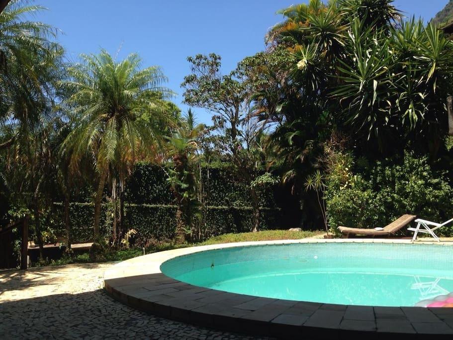 Visão da piscina que fica no andar térreo junto com o bar e a sauna com banheiros e churrasqueira a gás .