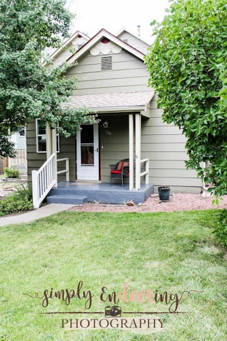 Another angle from outside of the home, With a hand rail and a nice chair to relax on the Porch on a warm sunny day in CO Springs.